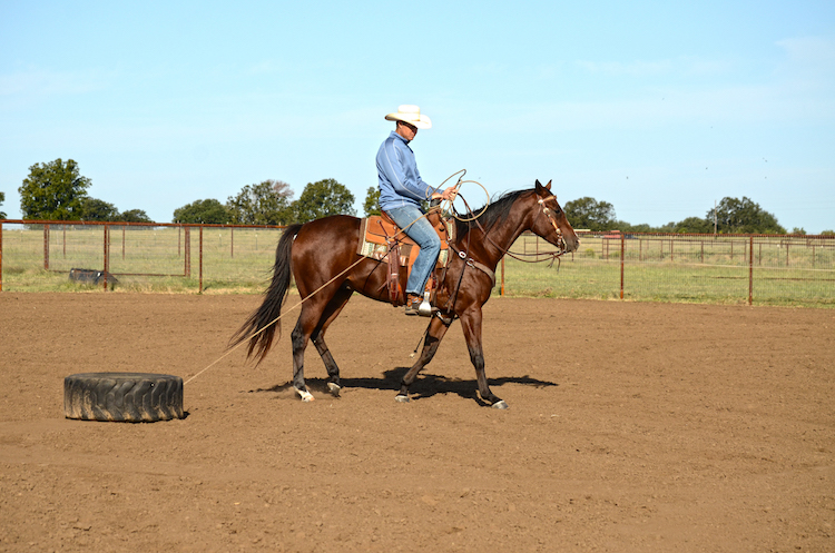Justin Briggs pulling tire on horseback