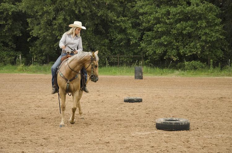 Danyelle Campbell walking around tires horseback