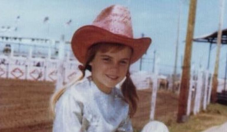 Ann Lewis sitting on fence at barrel race