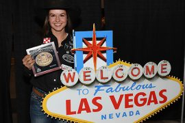 Hailey Kinsel standing with Las Vegas Sign holding world champion WNFR buckle