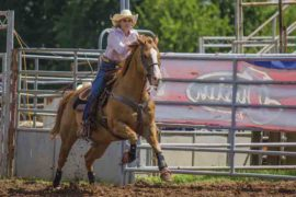 girl riding a horse during a barrel race
