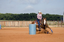 Lacey Harmon turning barrel on futurity horse