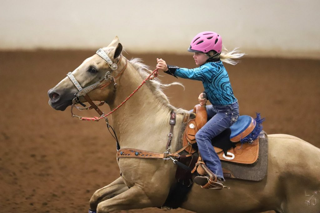 Little girl on palomino leaving the barrel
