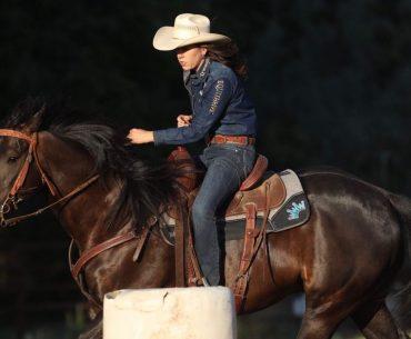 Nellie Miller riding Cowboy around a barrel