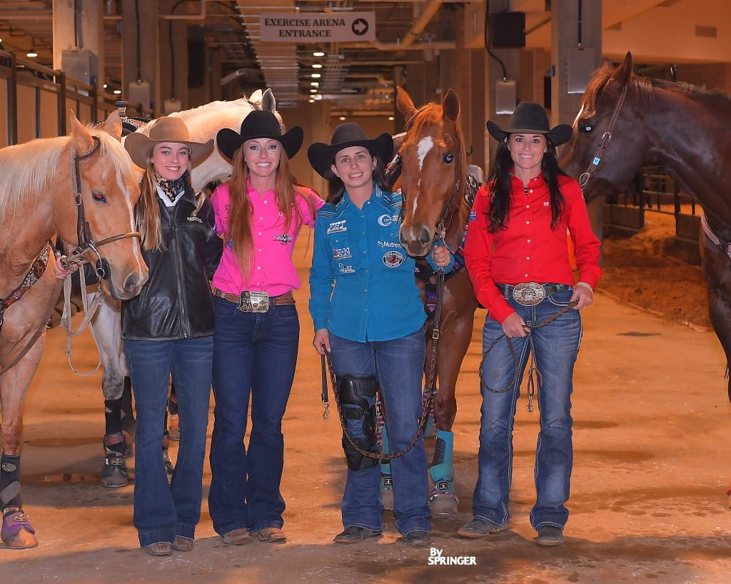 barrel racers standing in the barn with their horses