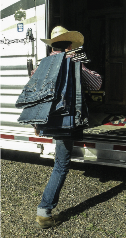 boy walking into trailer tack room carrying jeans