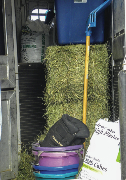 storage compartment of trailer packed with hay and buckets