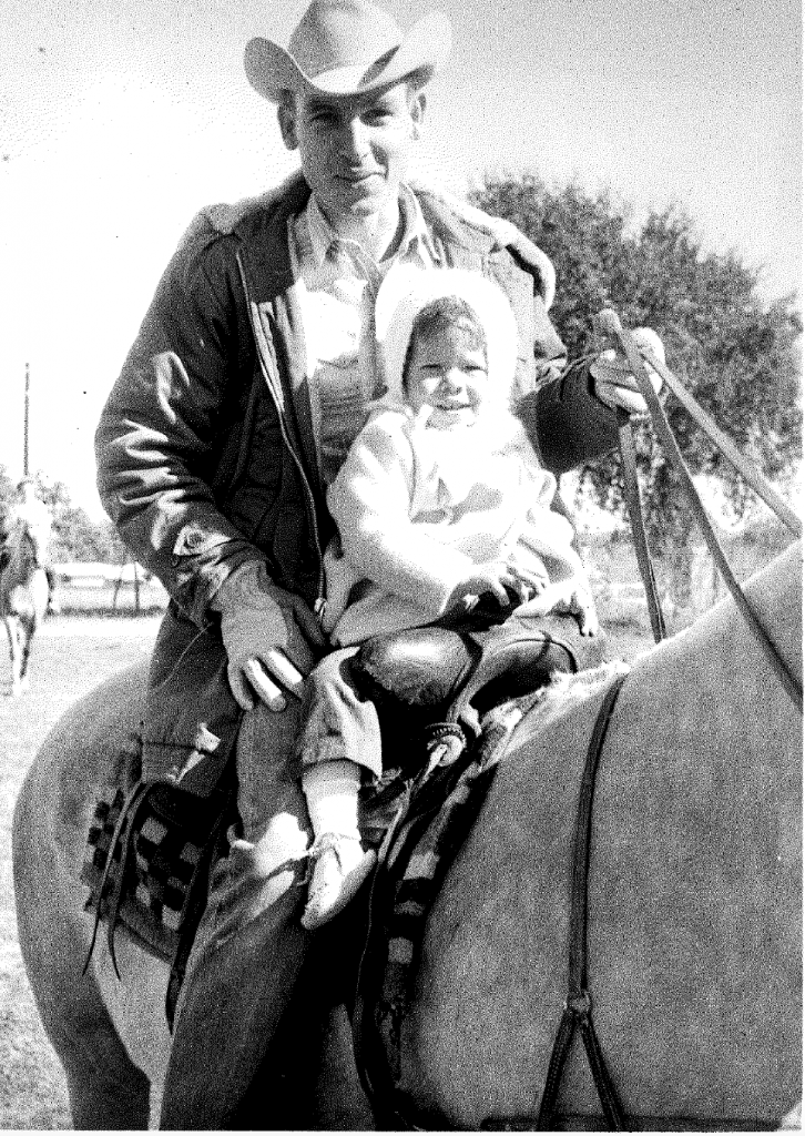 father with young baby sitting in front of him on horse