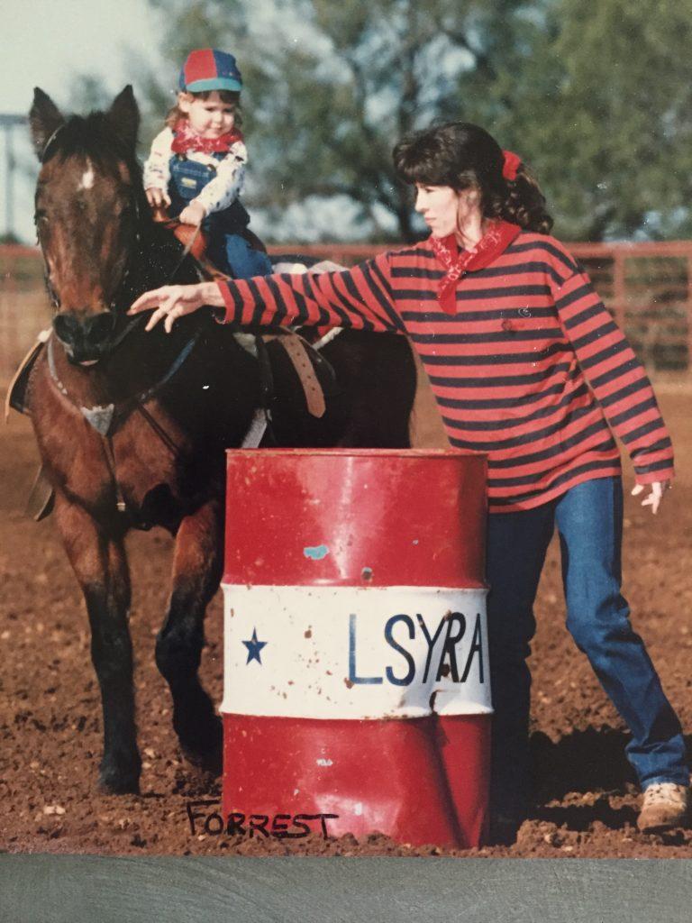 mom leading daughter on pony around barrel
