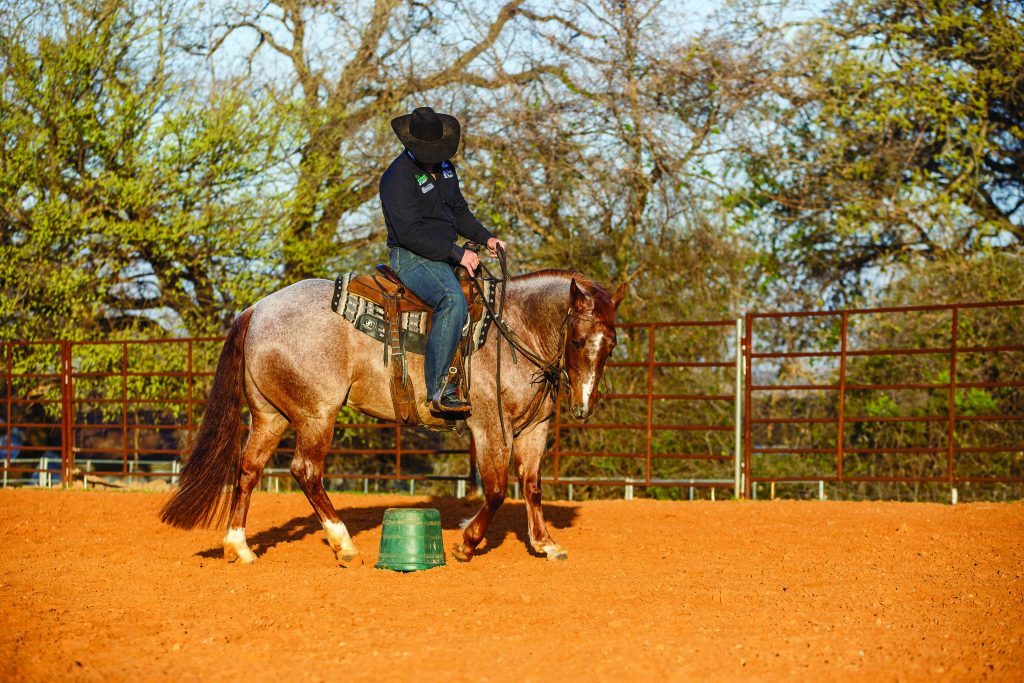 Rhett Baker turning a horse around a bucket