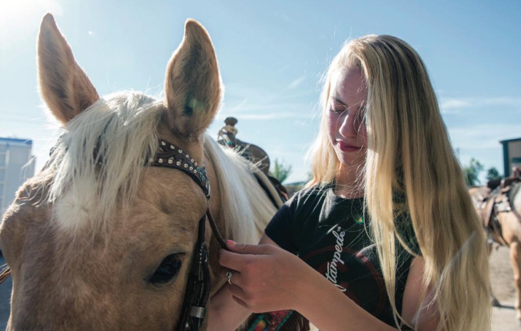 teenage girl buckling bridle on horse
