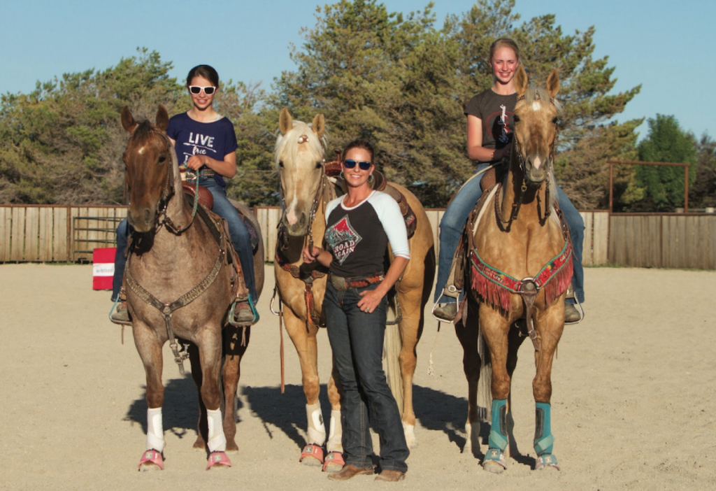 Jessie Telford standing with her daughters in the arena