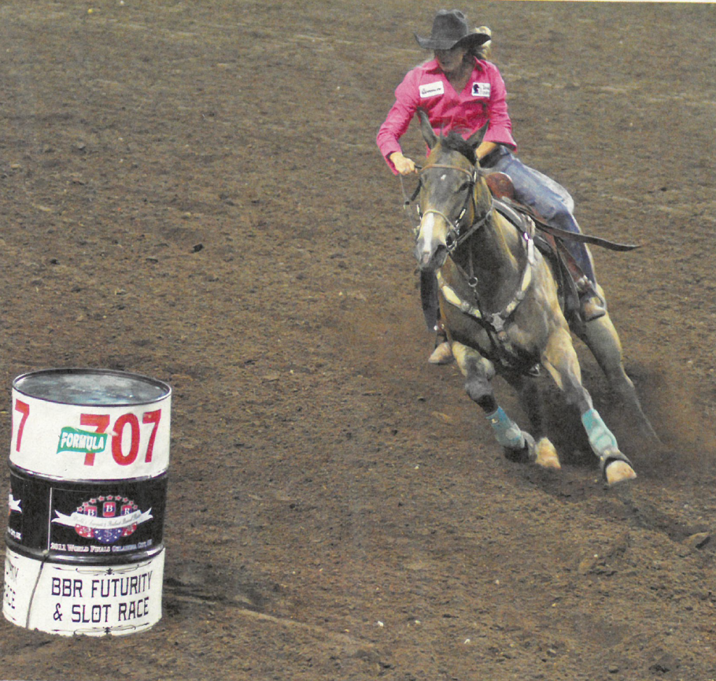 Kassie Mowry guiding a horse into the first barrel turn