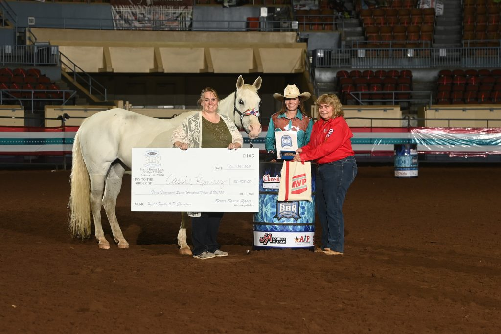 Cassie Ramirez standing with Maggie Mae horse and winner's check